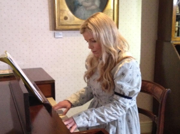 Ellie Harrison in costume, playing the Clementi square piano at the Museum for BBC One's Countryfile